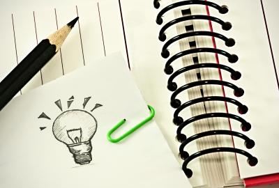 Jegyzettömb és a beszúrt jegyzet egy kis villanykörtével: itt teremnek az ötletek!